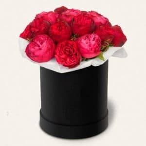 Красные пионовидные розы в черной шляпной коробке