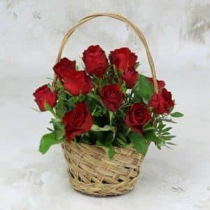15 красных роз с листьями фисташки в корзине.